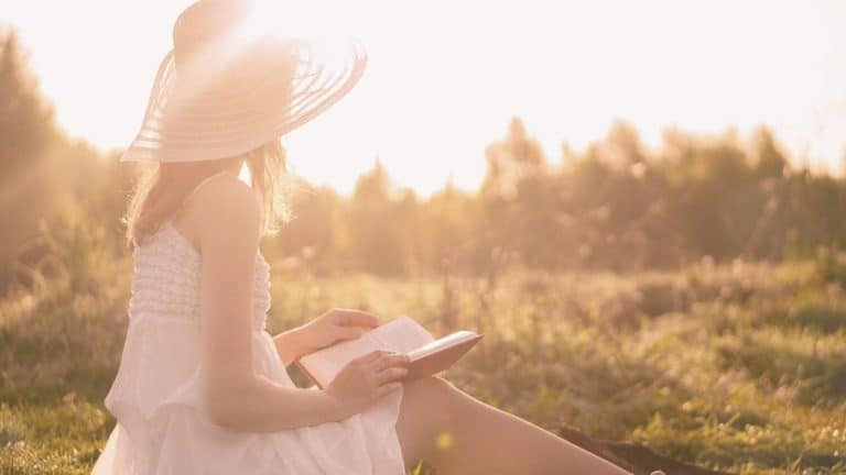 woman big hat sitting in field reading a book