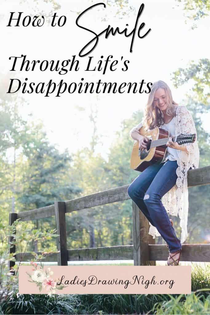 girl sitting on rail fence playing guitar
