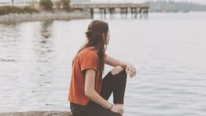 young woman sitting on dock